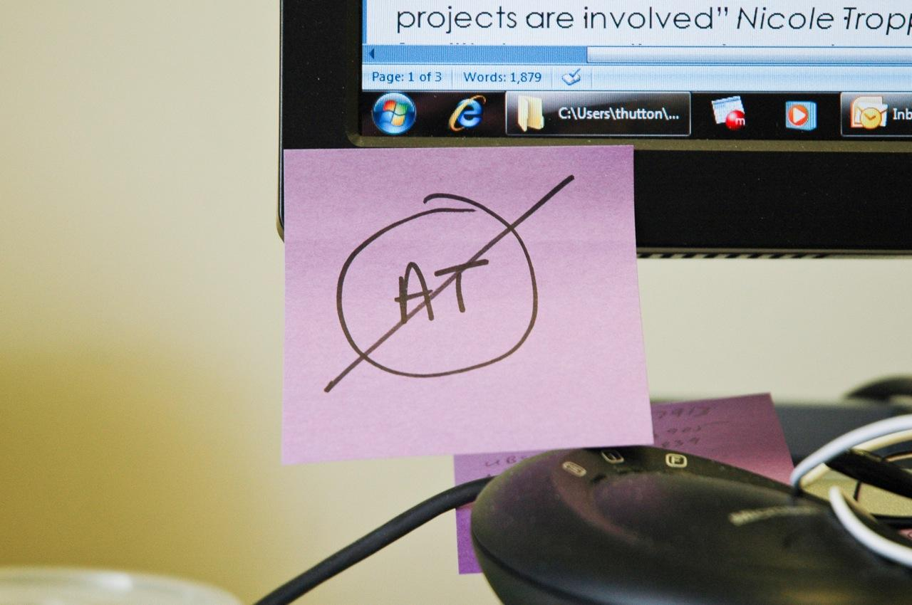The word AT crossed out, written in marker on a sticky-note attached to a computer screen