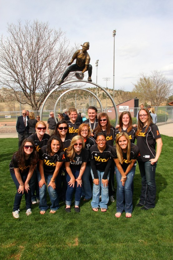 The softball team posed in front of the sculpture
