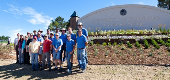 Partners, participants, and landscaping crew in front of the west entrance sign