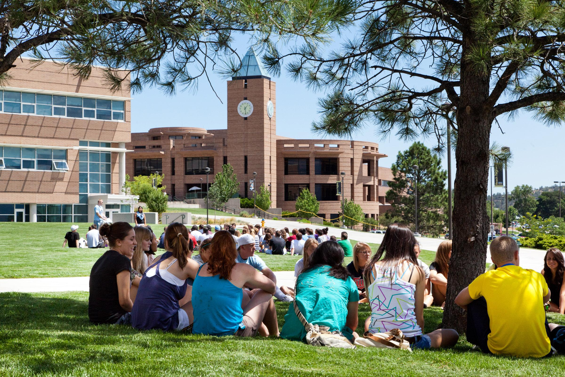 Students sit on the grass with El Pomar Center bell tower behind them