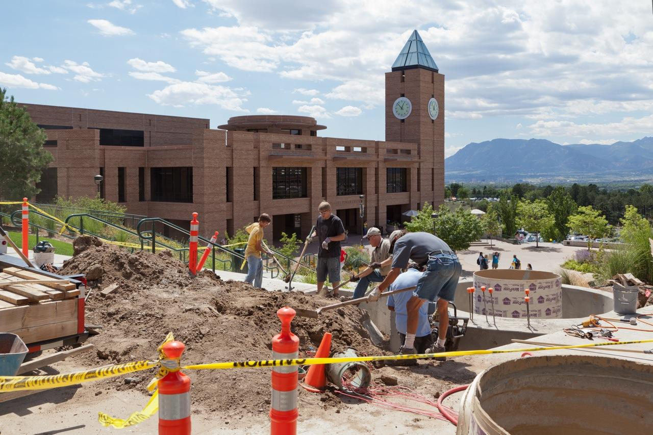 Contractors prepare a concrete mounting base near the northeast corner of the Osborne Center, El Pomar Center / Kraemer Family Library in the background