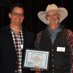 Dave Khaliqi, left, accepts a Distance Learning of the Year Award from Floyd Beard.