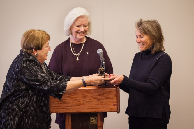 Chancellor Pam Shockley-Zalabak, left, presents Johnson Foundation Trustee Lynn Campion with a bronze mountain lion while Nancy Smith, dean, Helen E. and Arthur Johnson Beth-El College of Nursing and Health Sciences, watches the presentation.