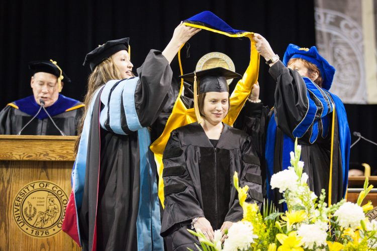 Carrie Arnold, assistant director, Freshman Seminar Program and Honors Program, receives her hood during May 13 graduation ceremonies.