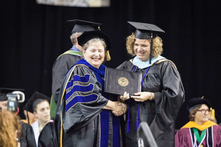 Interim Provost Terry Schwartz presents Mollie Sutherland, right, with her degree at May 13 ceremonies.