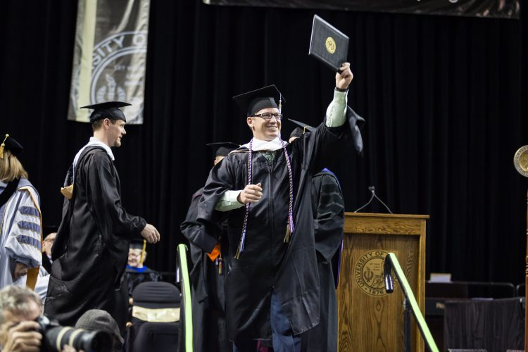 A master's student receives his degree during the 2018 spring commencement ceremony