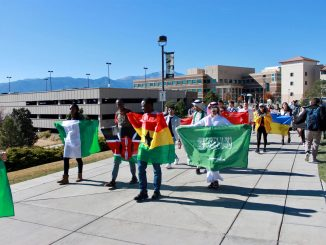 International students walk with flags at UCCS