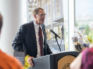 Dean Ferris speaks at a podium during a welcome reception