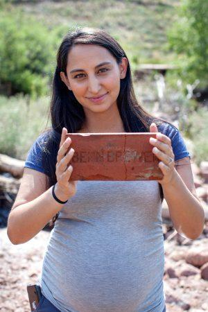 Anna holds up an old red brick with lettering embossed