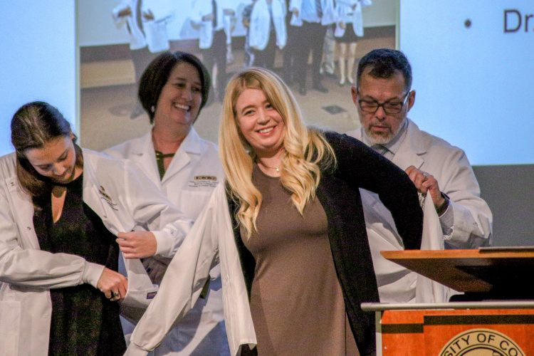 Student puts on white coat during ceremony.