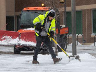Facilities Services crew member shovels snow Feb. 18.