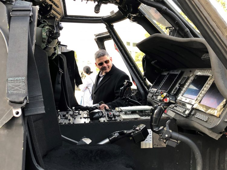 Chuck Litchfield looks inside a helicopter cockpit