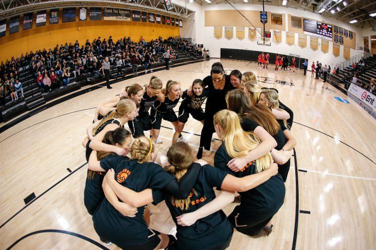 Women's team huddle on Blackout Night, Feb. 8.