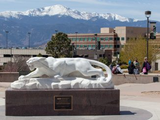 Mountain lion statue with Pikes Peak