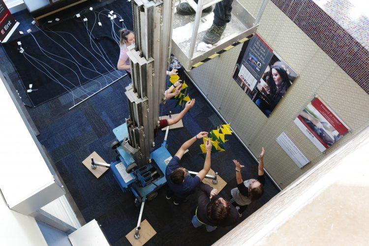 VAPA students hanging the work