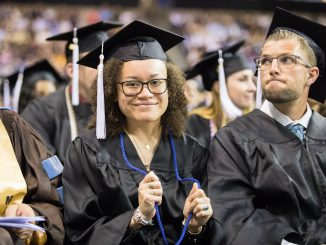 A student holds her blue contribution cord