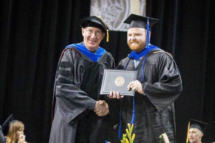Beau Kelly receives his master's degree at the 2019 spring commencement.