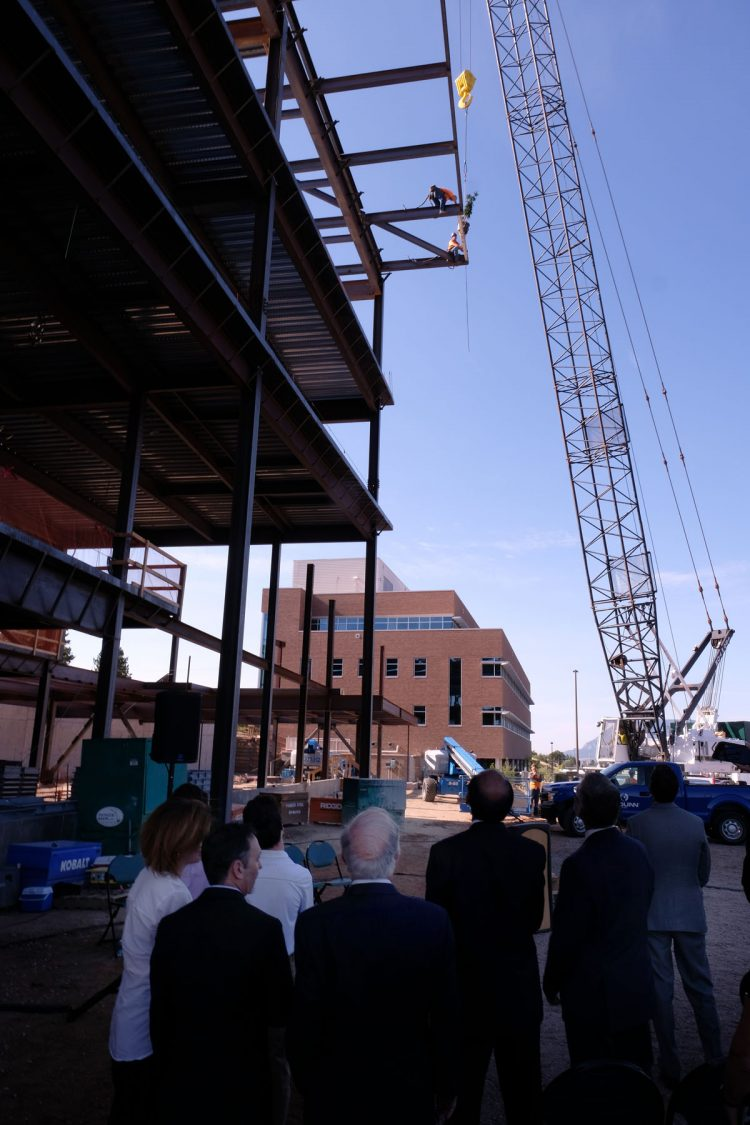 Crews from Pioneer Steel place the final piece of steel on the William J. Hybl Sports Medicine and Performance Center during the beam topping off ceremony July 31.