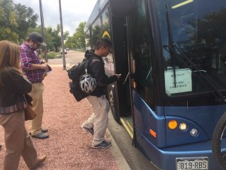 A student steps onto a Mountain Metro bus heading to campus.