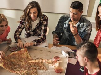 Students huddle around a pizza