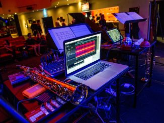 A laptop and instruments are set up before a performance.