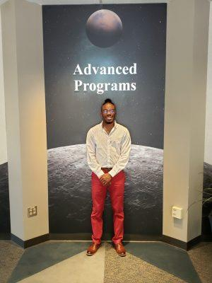 Chris Boles poses with his signature bright red work shoes, which he was wearing on the day he was named one of Lockheed Martin's most influential interns.