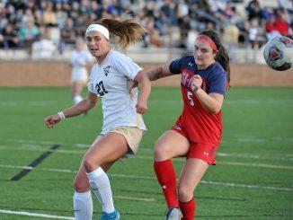 Kaitlin Hinkle kicks the ball against a CSU-Pueblo defender