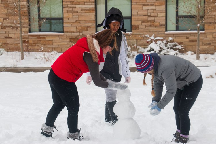 Residence hall students build a snow man during a snow day Oct. 28.