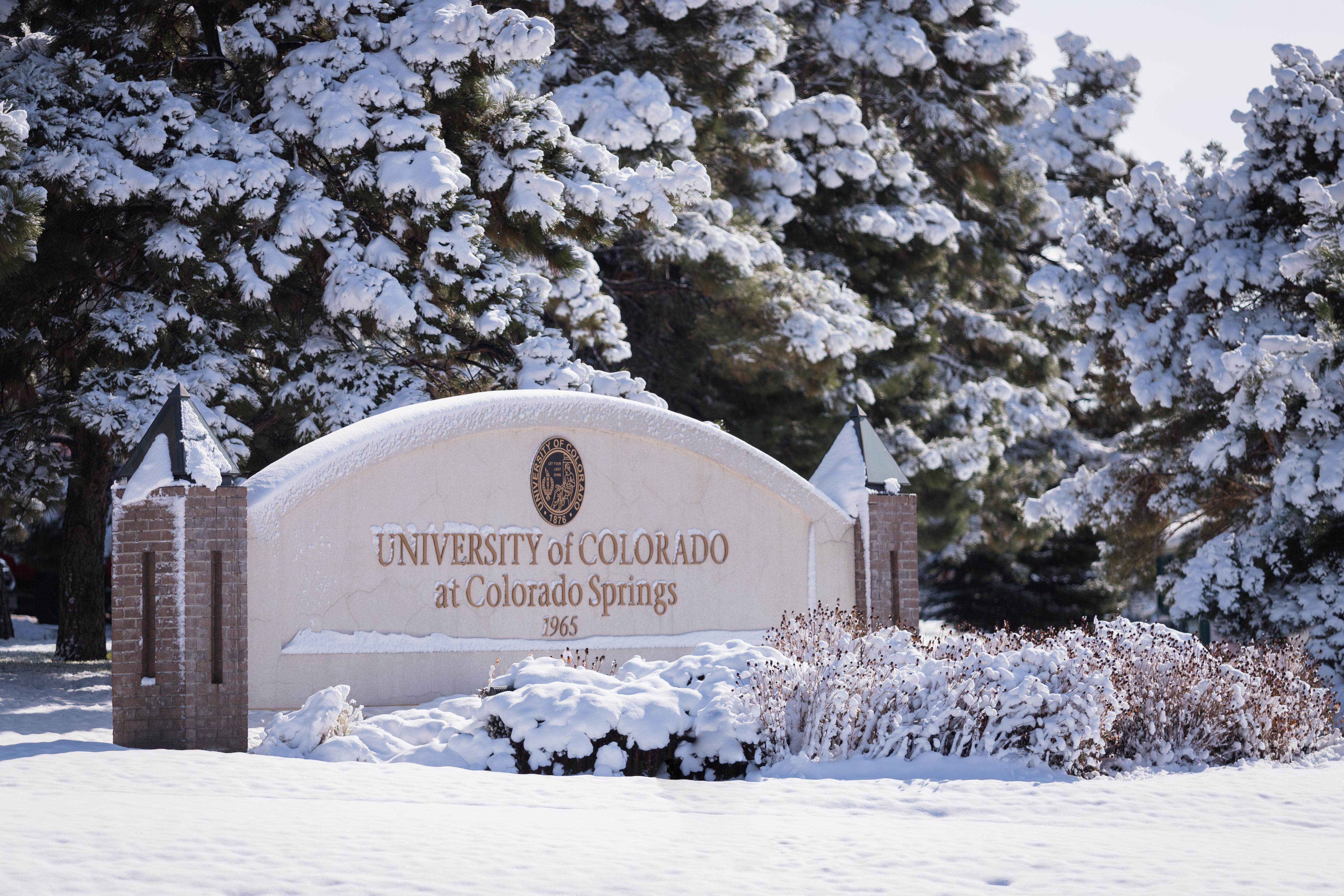 An entrance sign to campus is covered in snow.