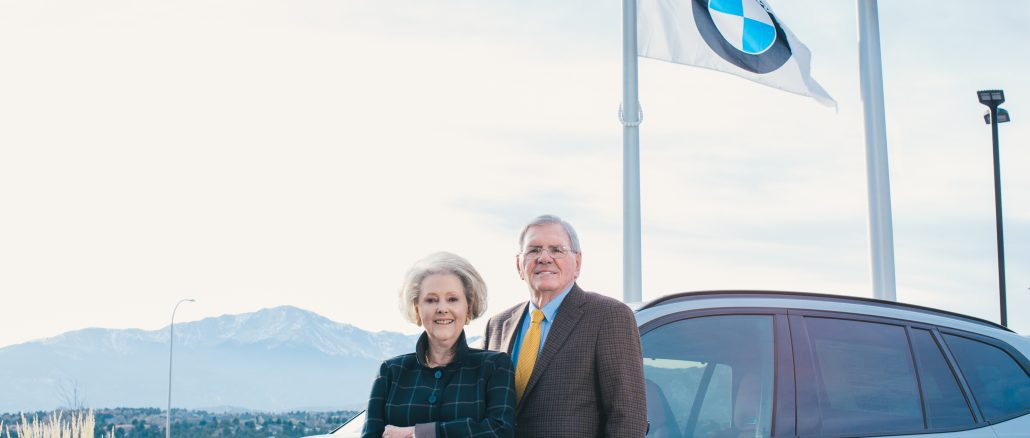 Phil and Ann Winslow standing in front of a car with a BMW flag and Pikes Peak in the background