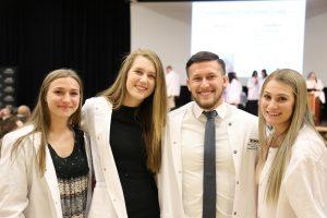 Four students pose for a group picture after the White Coat Ceremony.