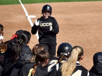 A softball student-athlete jogs to home plate after a home run.