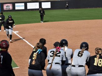 A softball student-athlete jogs to home plate where her teammates are gathered.