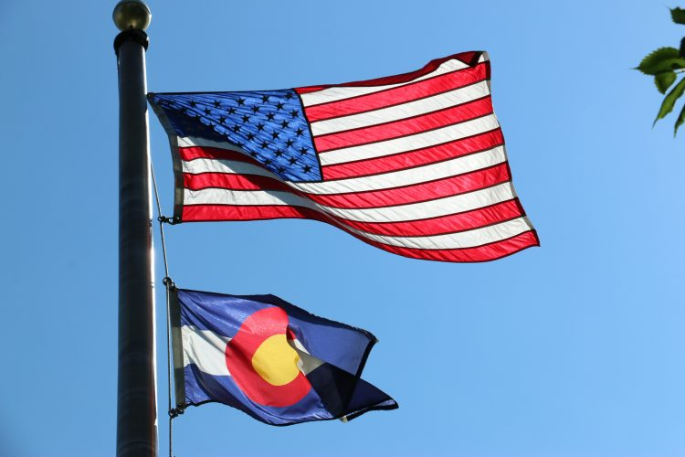 The United States and Colorado flags fly in the wind.