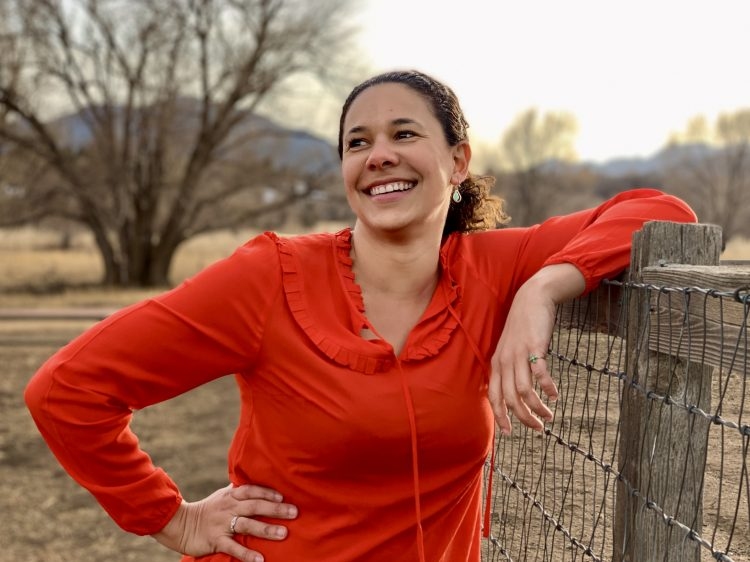 Professor Cerian Gibbes poses for a photo in a bright red blouse. She is leaning on a wood and wire fence in a field in winter.