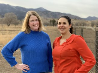 Professors Emily Skop and Cerian Gibbes pose in bright sweaters in front of a wintry field.
