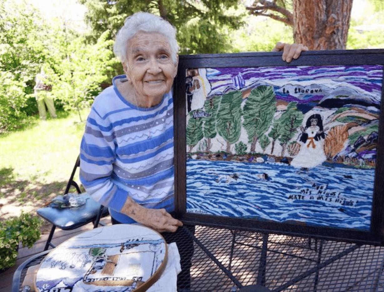 Josephine Lobato holds a piece of artwork.