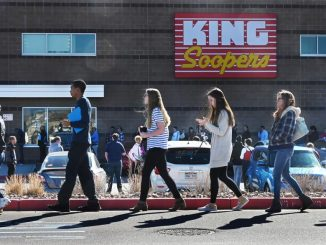 People line up in front of a King Soopers grocery store.