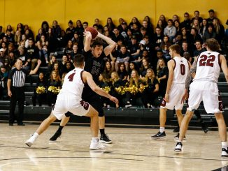 Ed Bourke holds the ball against a defender from Colorado Mesa.