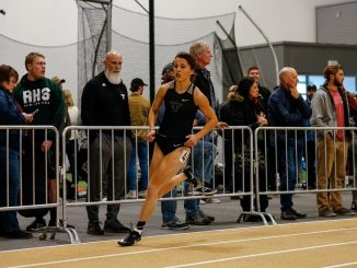 Kaija Crowe rounds the corner in lane four in Mountain Lion Fieldhouse