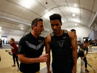 Coach Ross Fellows talks to Will Ross during a meet in Mountain Lion Fieldhouse