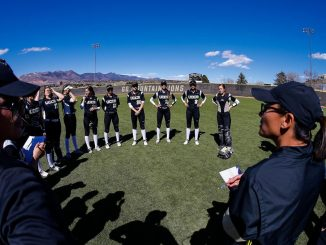 The softball team gathers in a circle for instructions from the coach at Mountain Lion Field