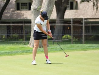 A women's golfer hits a putt on the green.