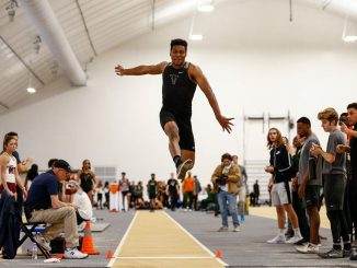 William Ross in midflight in the triple jump at Mountain Lion Fieldhouse.