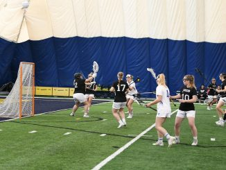 Lacrosse players in front of a goal in an inflatable building.