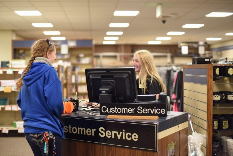 A student works at a customer service desk in the bookstore.