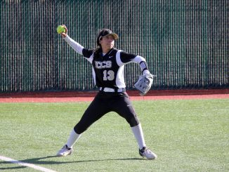 Brianna Santos throws the ball from left field at New Mexico Highlands.
