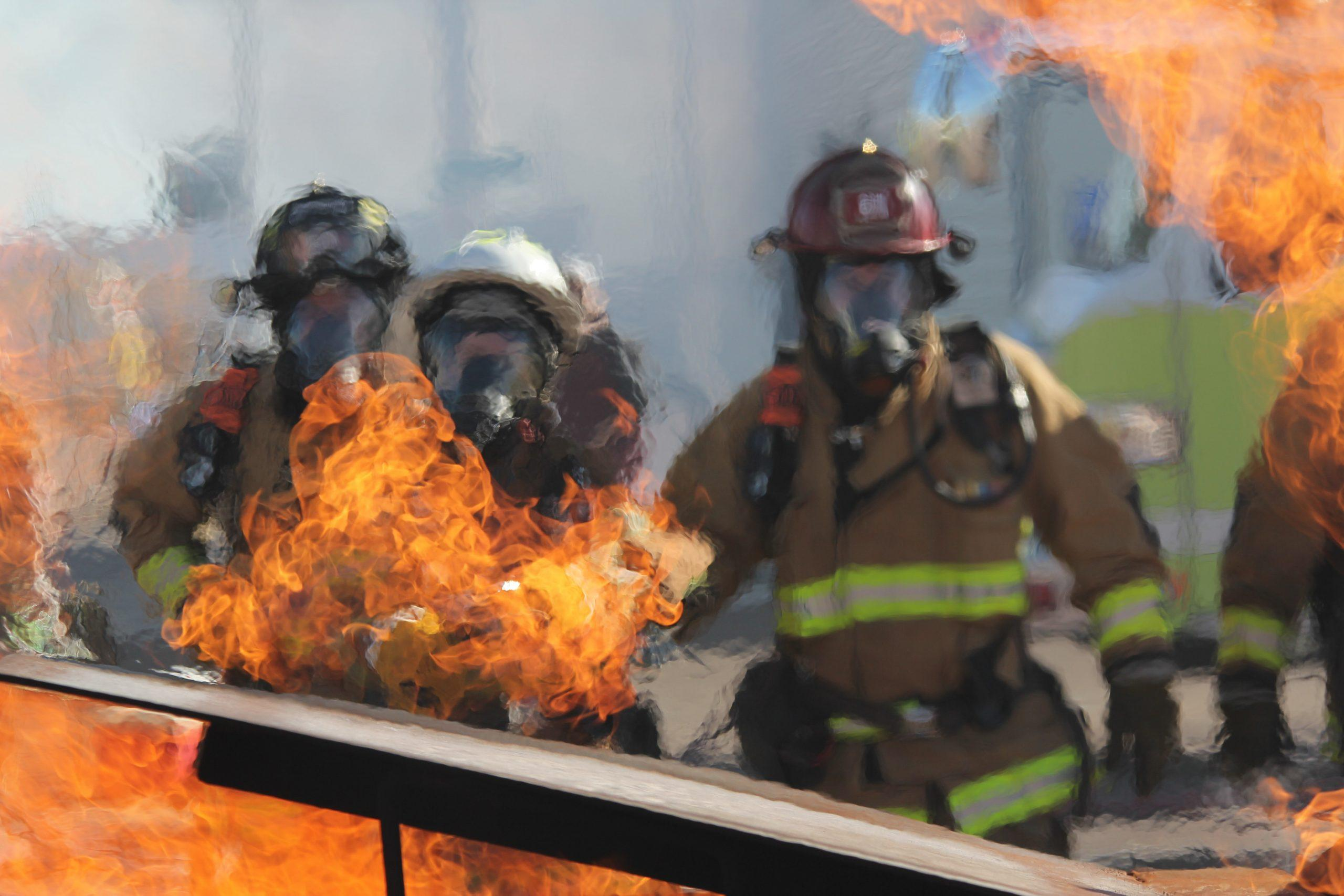 A team of firefighters drill on a training fire.