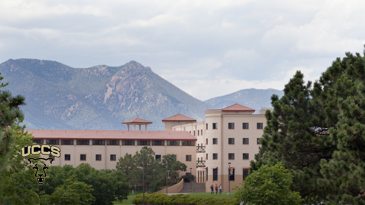 Summit Village residence halls are framed by trees with the Rampart Range mountains in the background