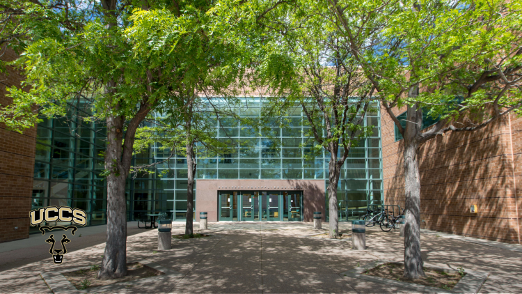 The main entrance to the Engineering and Applied Science building with leaves on the trees in front of the building